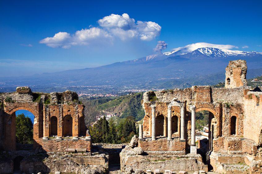 19312783 - ruins of the greek roman theater with etna erupting, taormina, sicily, italy