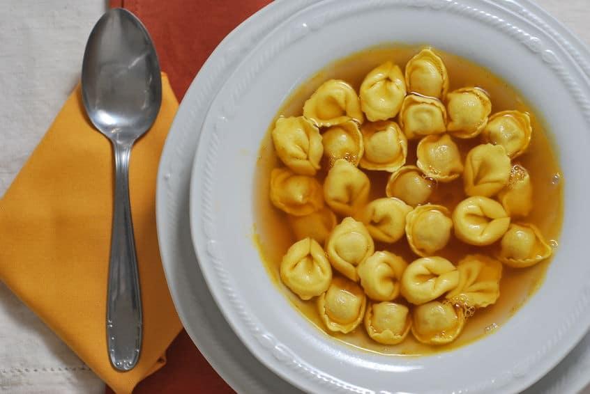 31767156 - tortellini soup in white plate