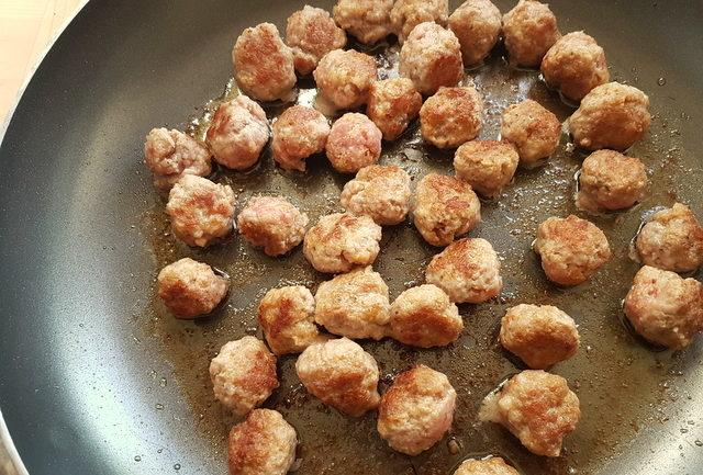 veal meatballs cooking in frying pan