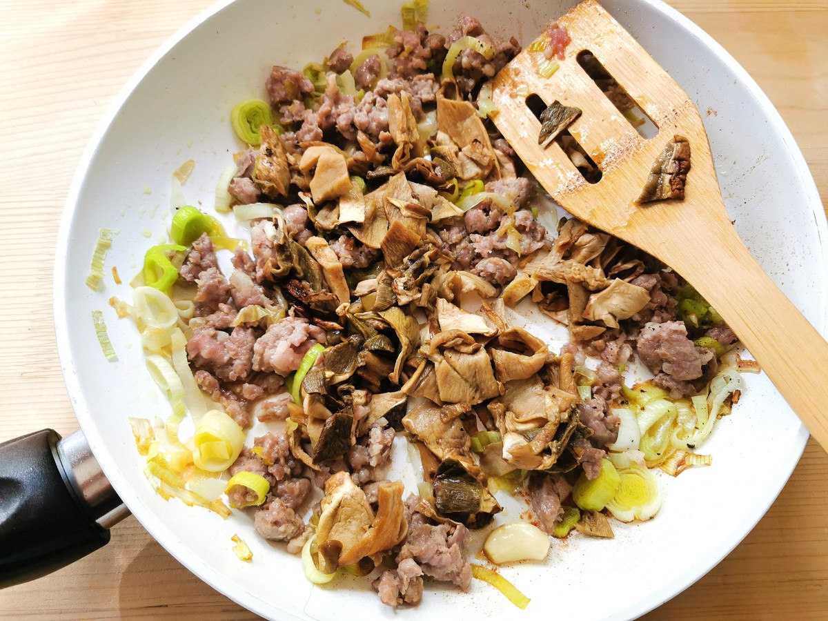 porcini mushrooms added to the sausage meat and leeks in frying pan