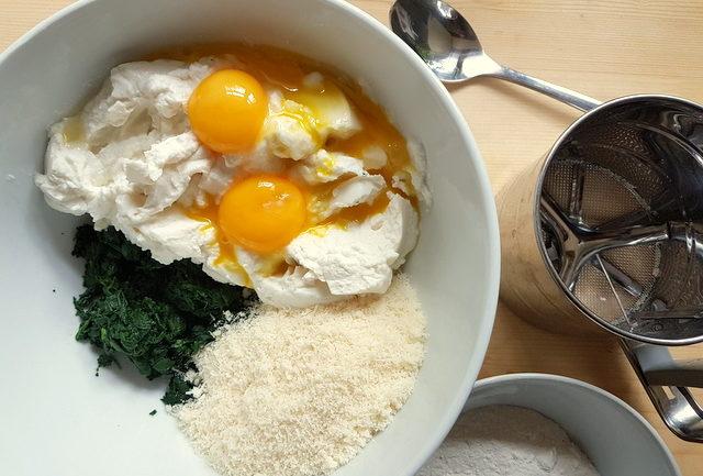 eggs, ricotta, spinach, Parmesan in white bowl for Tuscan gnudi (malfatti)