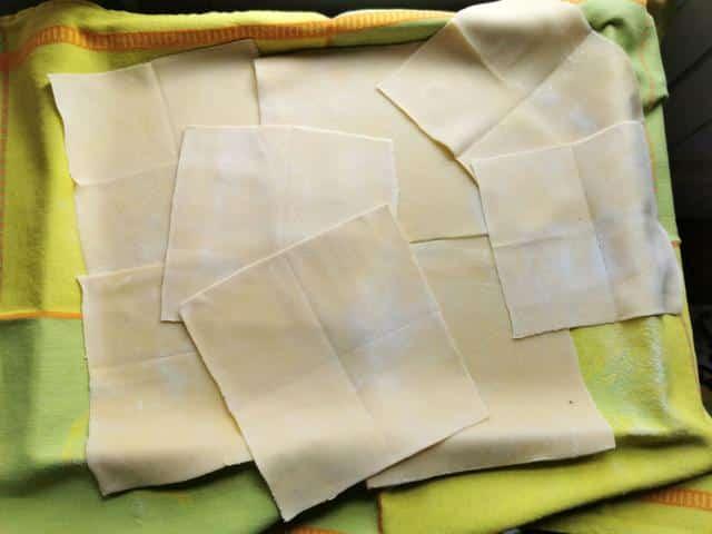 homemade handkerchief pasta squares (fazzoletti) on green tea towel