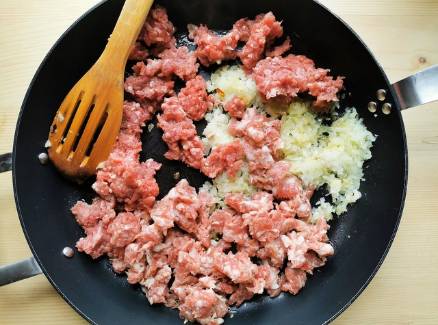 sausage meat, ground beef and onion cooking in skillet