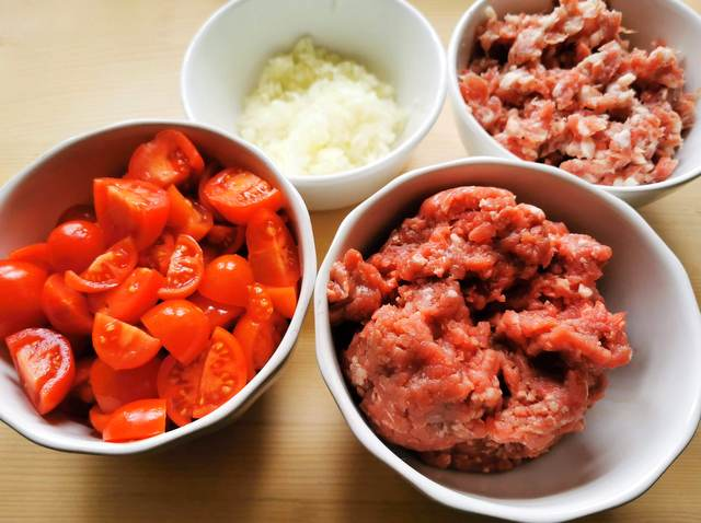 cut tomatoes, chopped onions, chopped sausage meat and ground beef in separate white bowls.