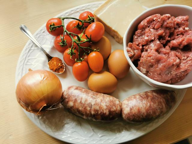 ingredients for beef and sausage ragu on white plate.