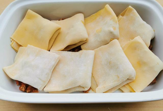 8 stuffed and folded fregnacce Abruzzesi in white oven dish.