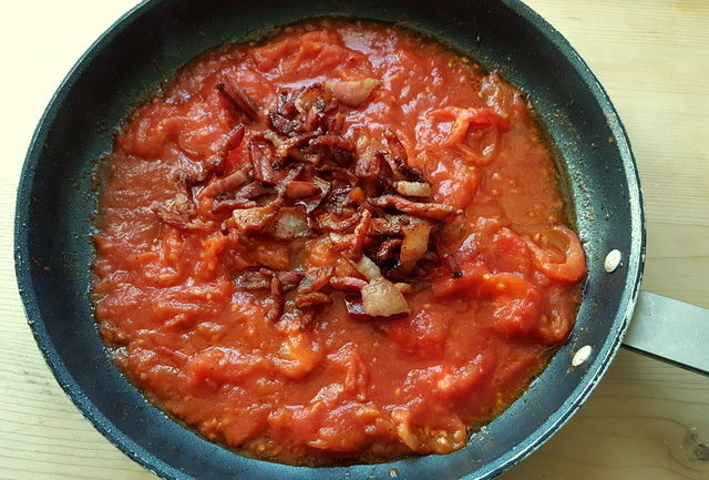 fresh tomato sauce and crispy pork cheek in frying pan