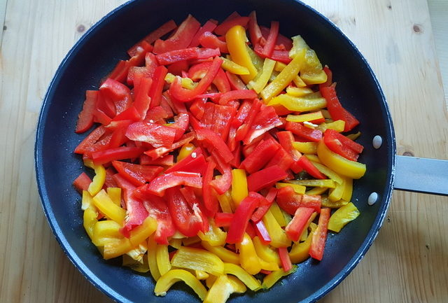 red and yellow bell pepper pieces in frying pan