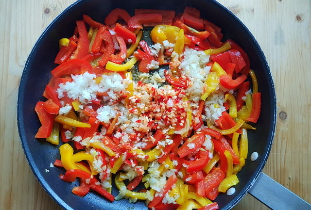 cut bell peppers, chopped onions, red chili pepper and garlic in frying pan