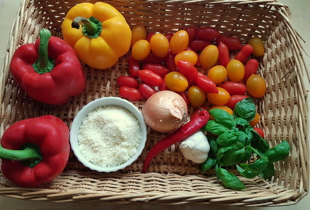 Ingredients for bucatini with red and yellow cherry tomatoes and peppers recipe in basket