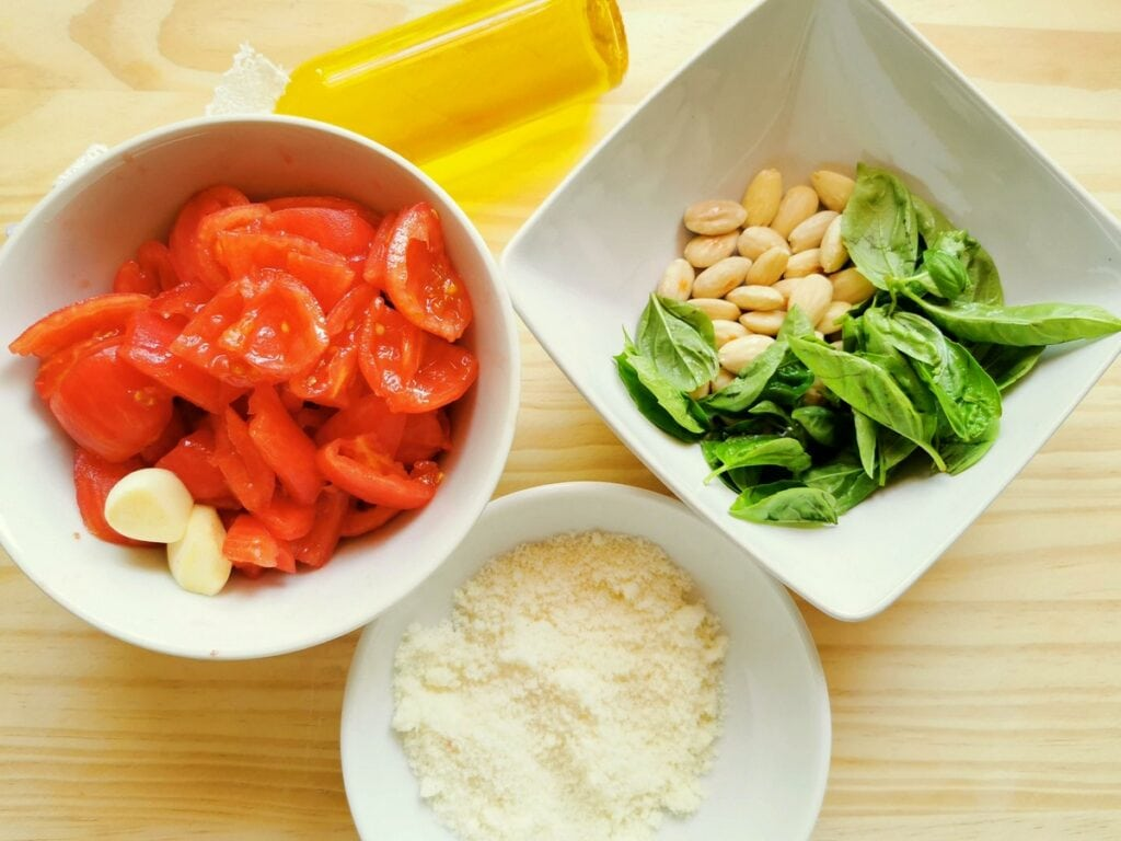 prepared ingredients for Trapanes pesto in white bowls.