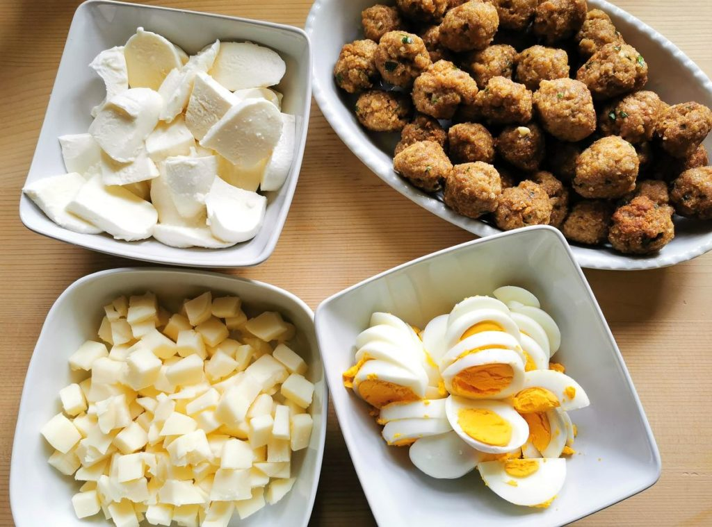 hard boiled eggs, cubed cheese and meatballs all in white bowls