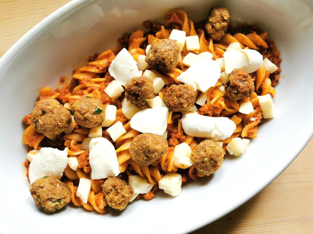 meatballs and cubed cheese scattered over pasta and ragu in oven dish