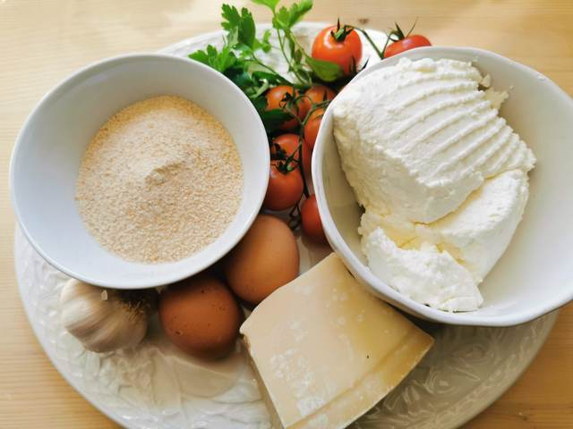 ingredients for ricotta balls in tomato sauce on white plate