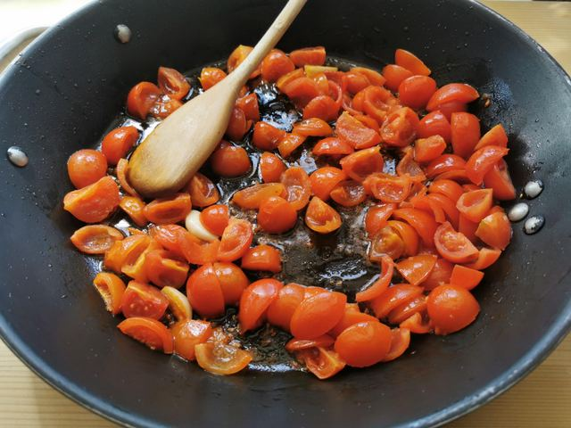 cherry tomatoes cooking in skillet