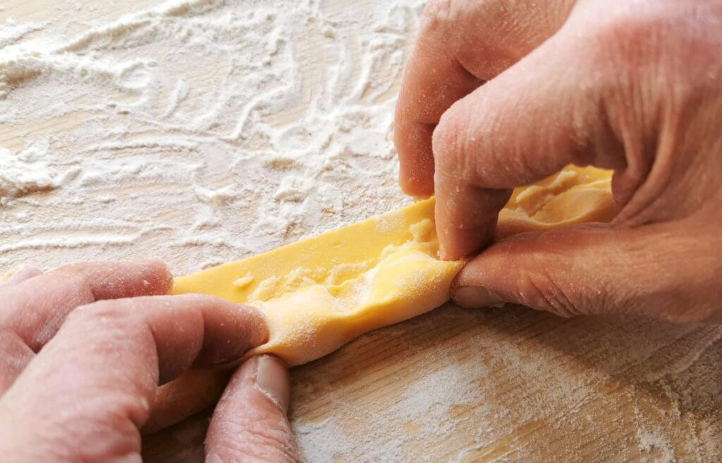 Pinching between each mound of filling to give them the agnolotti their distinctive shape