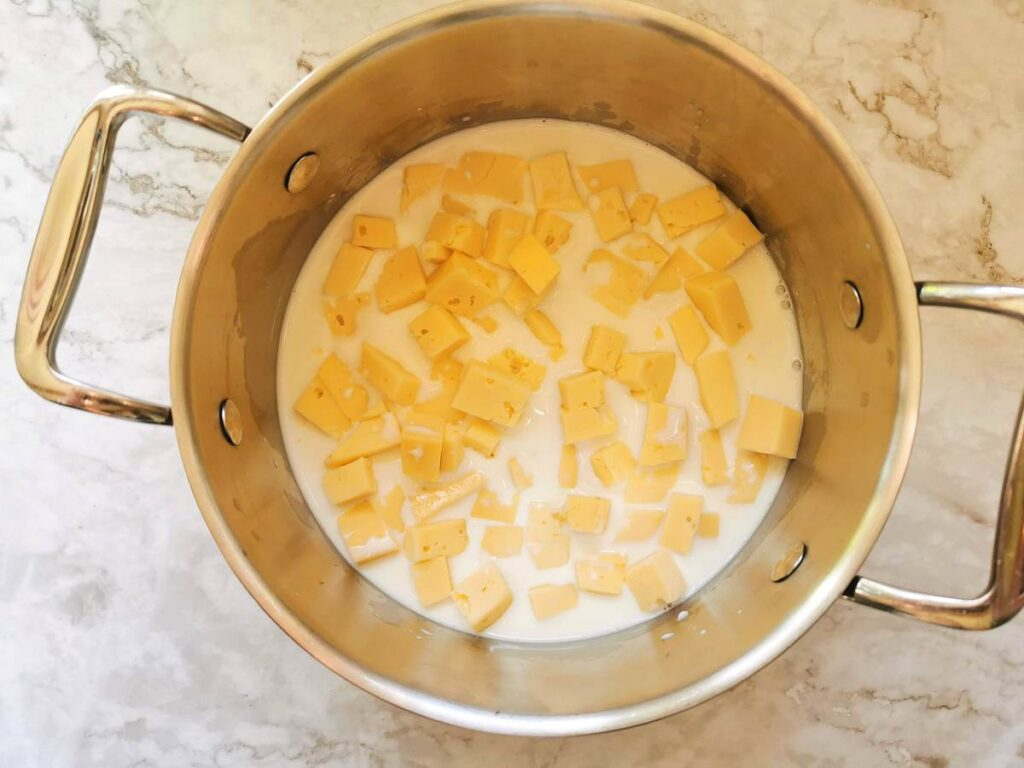 pieces of Fontina cheese in pan with milk.