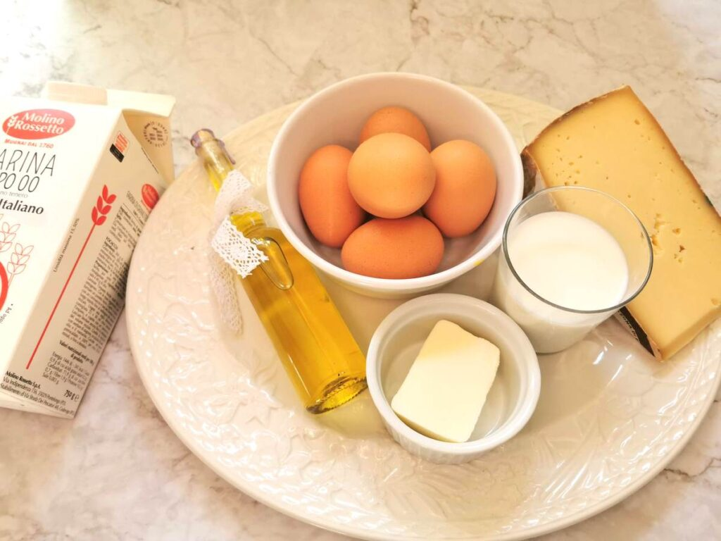 Ingredients for cheese stuffed agnolotti del plin on white plate