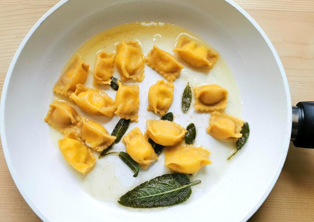 Cooked cheese stuffed agnolotti del plin in pan with melted butter and sage.
