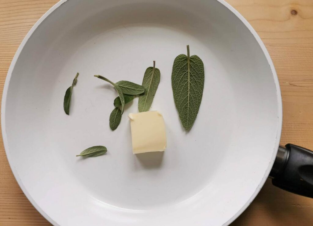 pieces of butter and fresh sage leaves in frying pan