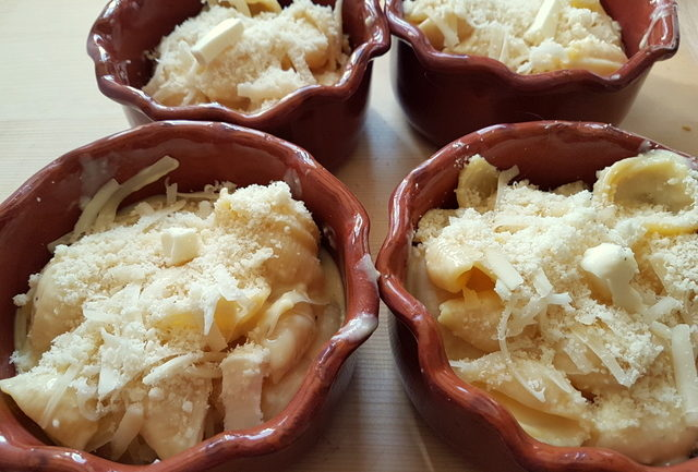 Cheesy conchiglie pasta al forno (baked pasta shells) in individual terracotta dishes before baking