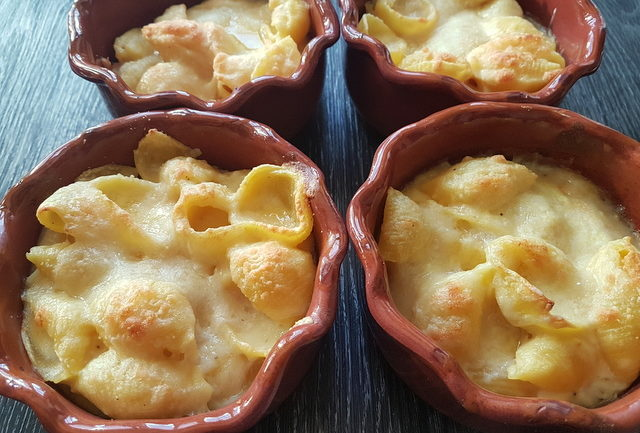 Cheesy conchiglie pasta al forno (baked pasta shells) in individual terracotta oven dishes