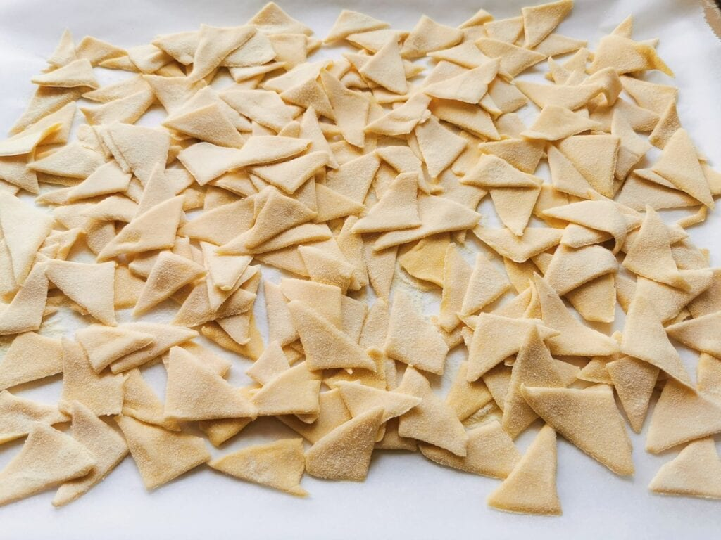 corn and wheat flour pasta triangles on white baking paper.