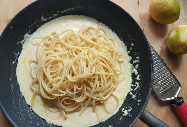 cooked linguine pasta and creamy lemon sauce in frying pan