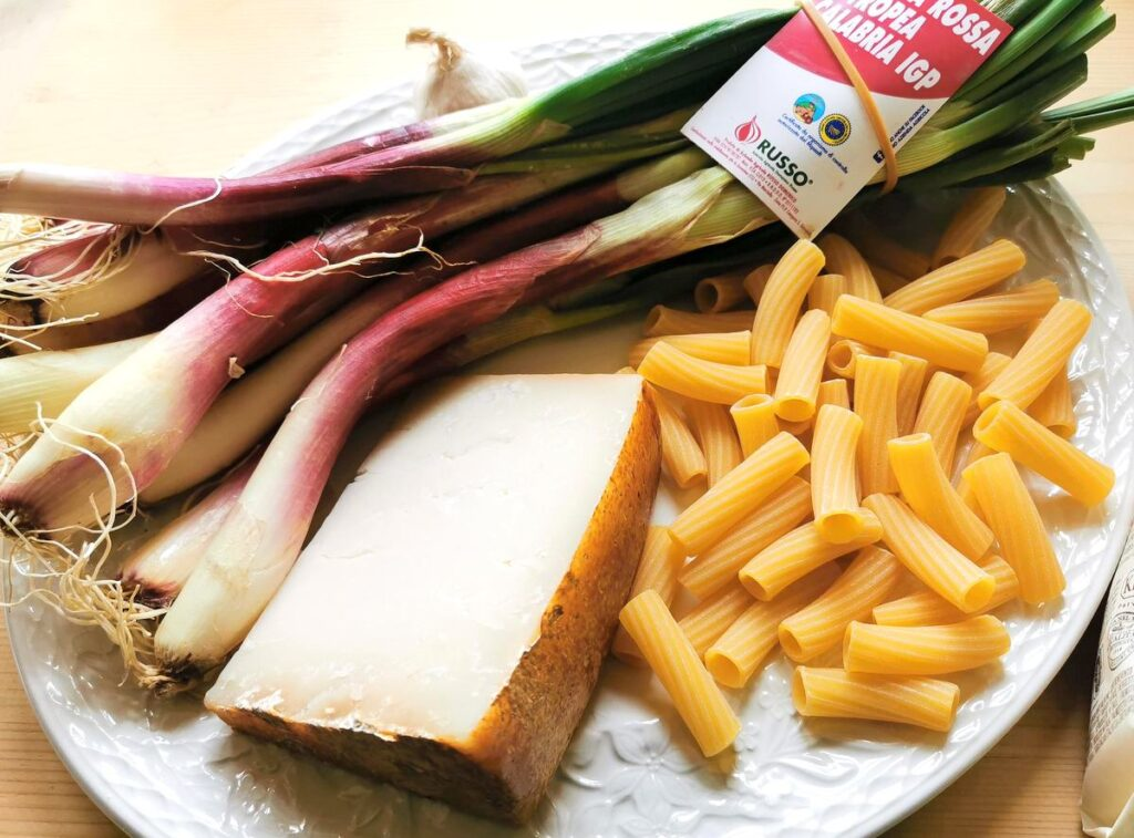 ingredients for elicoidali with tropea onions on white plate