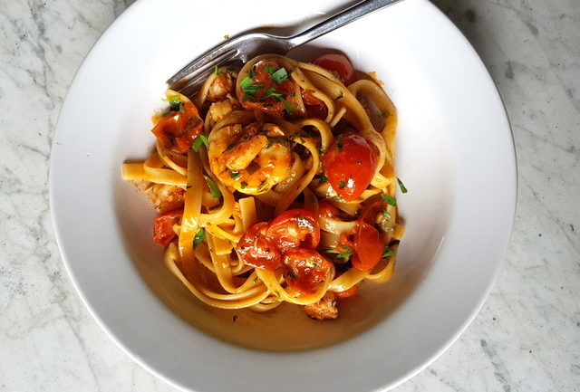 Fettuccine pasta with giant prawns and cherry tomatoes in white bowl