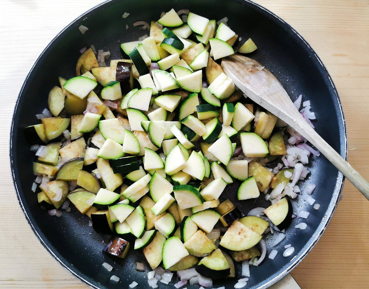 onions, eggplant and zucchini cooking in skillet