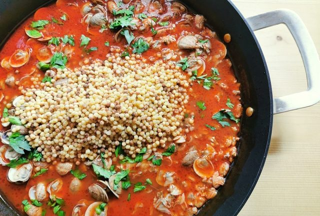 toasted fregola added to clams and tomato sauce in skillet