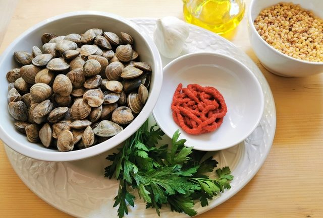ingredients for fregola with clams on white plate