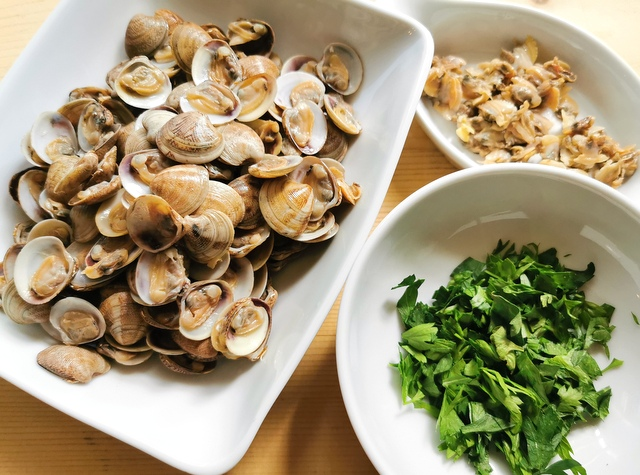 separated clams in a white bowl and chopped parsley in a white bowl