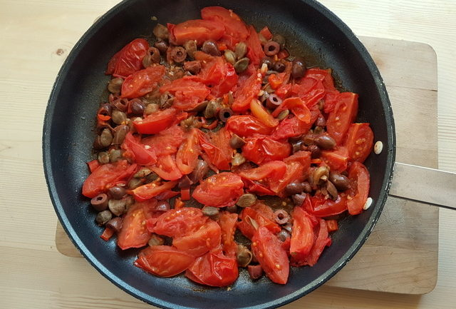 chopped tomatoes, olives and capers in frying pan