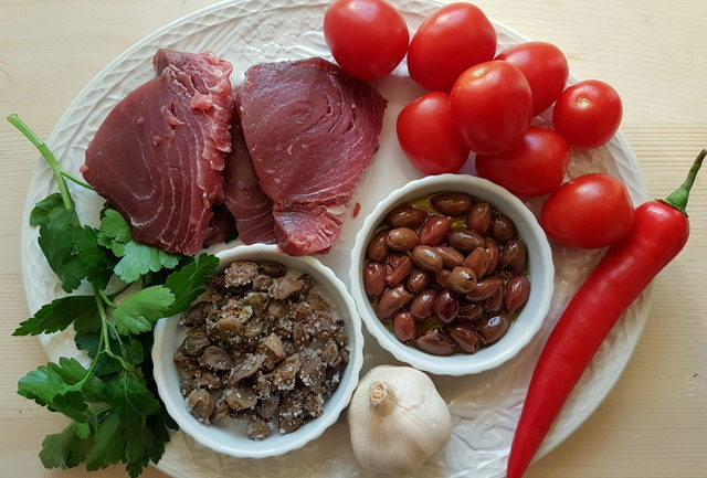 Ingredients for fresh tuna pasta all'eoliana on a white plate
