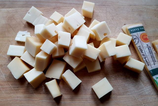 Fontina cheese cut into pieces on wooden board
