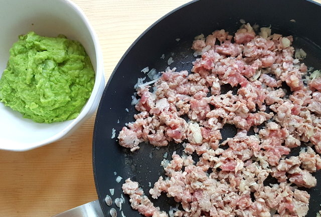 crumbled sausage meat and sliced onions in skillet next to pea puree in white bowl.