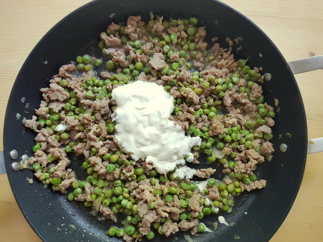 heavy cream added to sausage meat, peas and onions in skillet