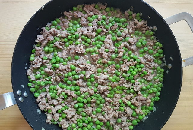 sausage meat, peas and onions cooking in skillet