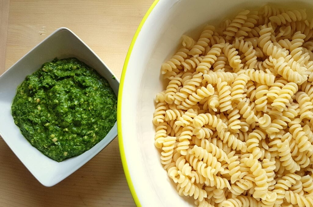cooked pasta in large bowl and ready pesto in small white bowl