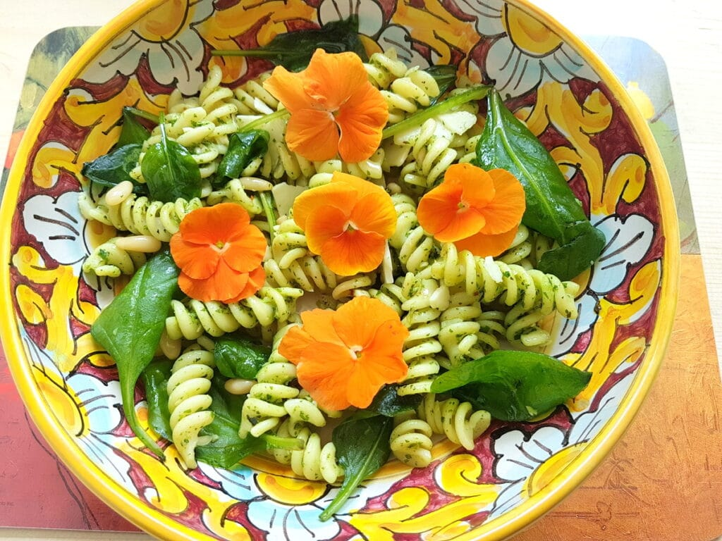 Green pasta salad with edible flowers