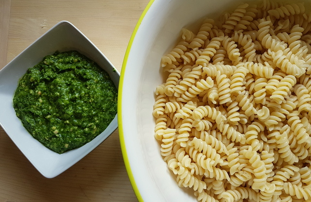 Green sauce in bowl and fusilli in bowl for green pasta salad