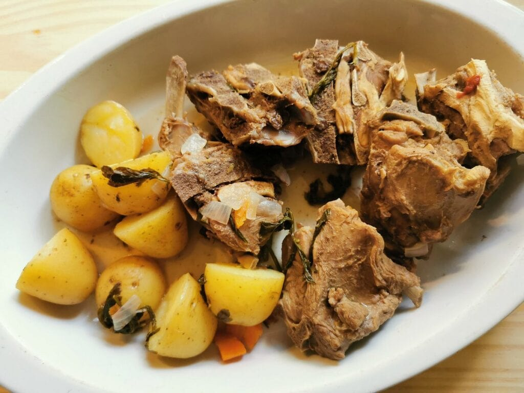 Cooked lamb neck bones and potatoes in a white dish