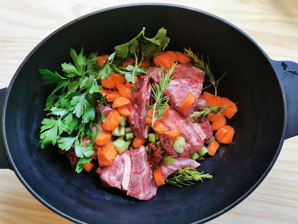 lamb neck bones with vegetables and herbs in Dutch oven
