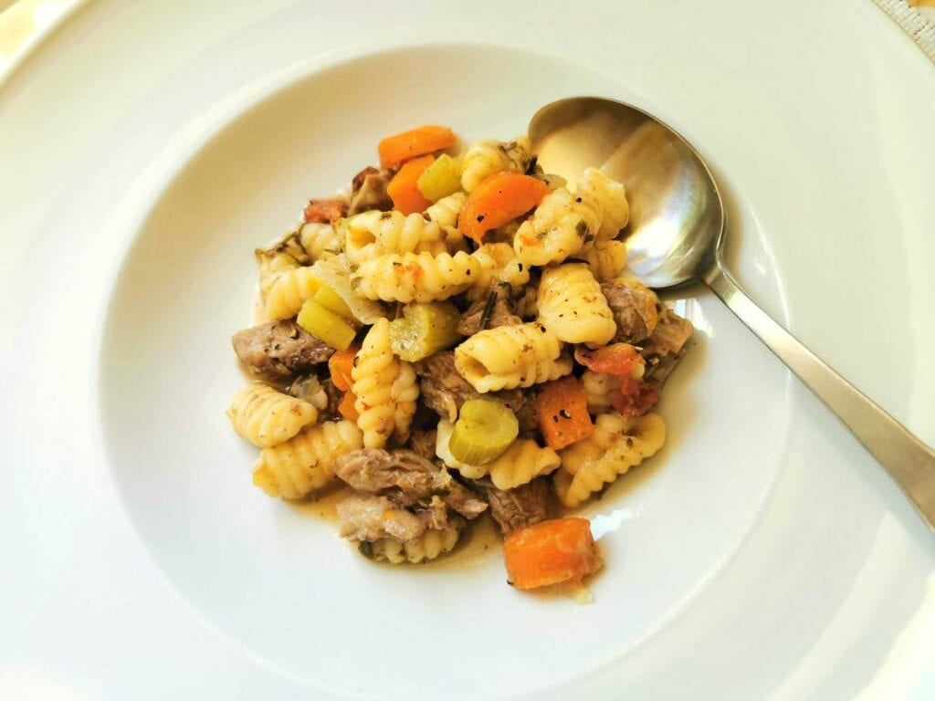 Homemade Sardinian gnocchi (malloreddus) in lamb broth.