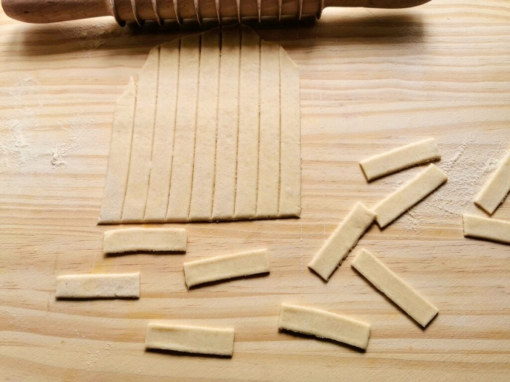 Sheet of rolled out dough cut into strips and small rectangles.