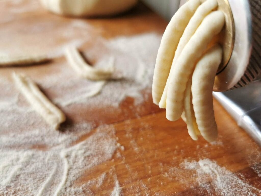 casarecce ready to be cut off from the front of the dough press.