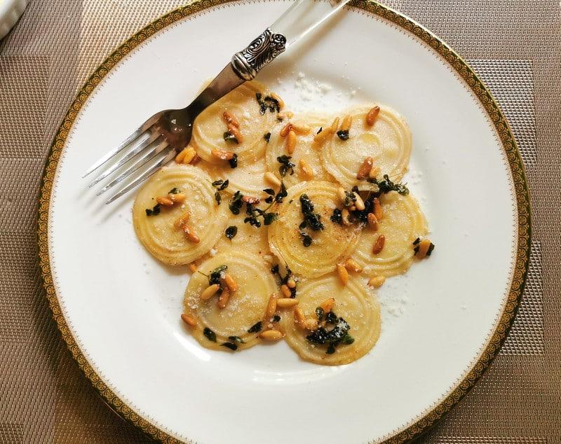 Homemade corzetti pasta with marjoram and pine nuts.