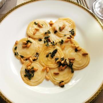Homemade corzetti pasta with marjoram and pine nuts